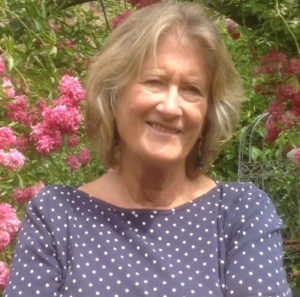A photo of our client Sue, in a garden