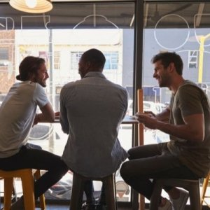 Three men sitting together in a cafe