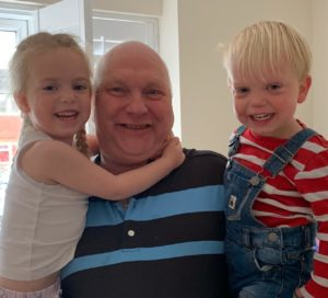 Photo of our client Mike holding his grandchildren