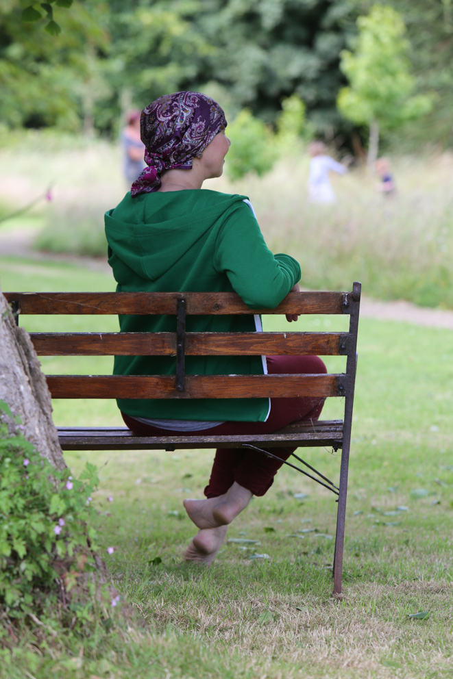 Client with head scarf sat on bench on retreat course