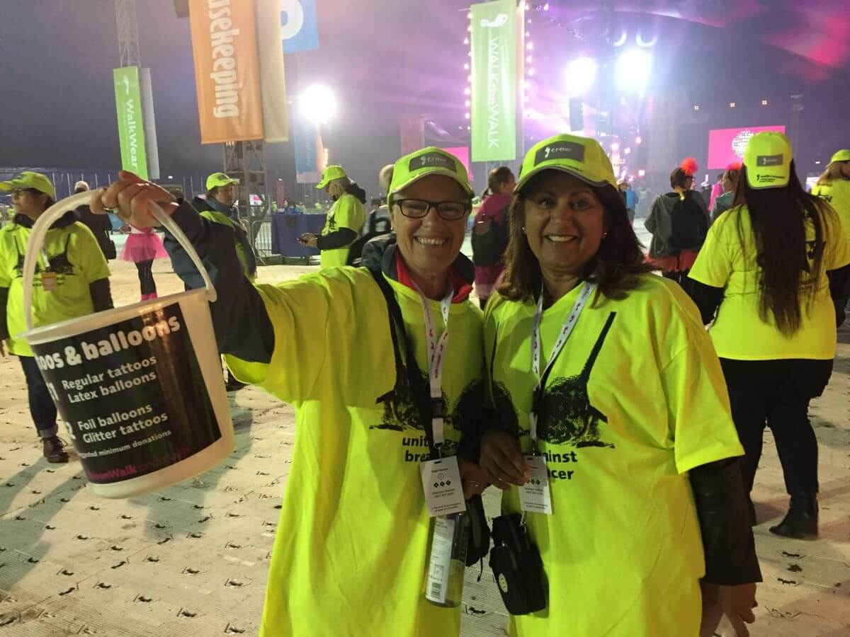 Photo from MoonWalk 2019 with two volunteers in yellow hats and t-shirts