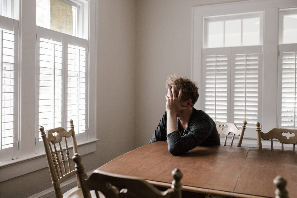 person holding head in hands leaning on a table, looking out of the window